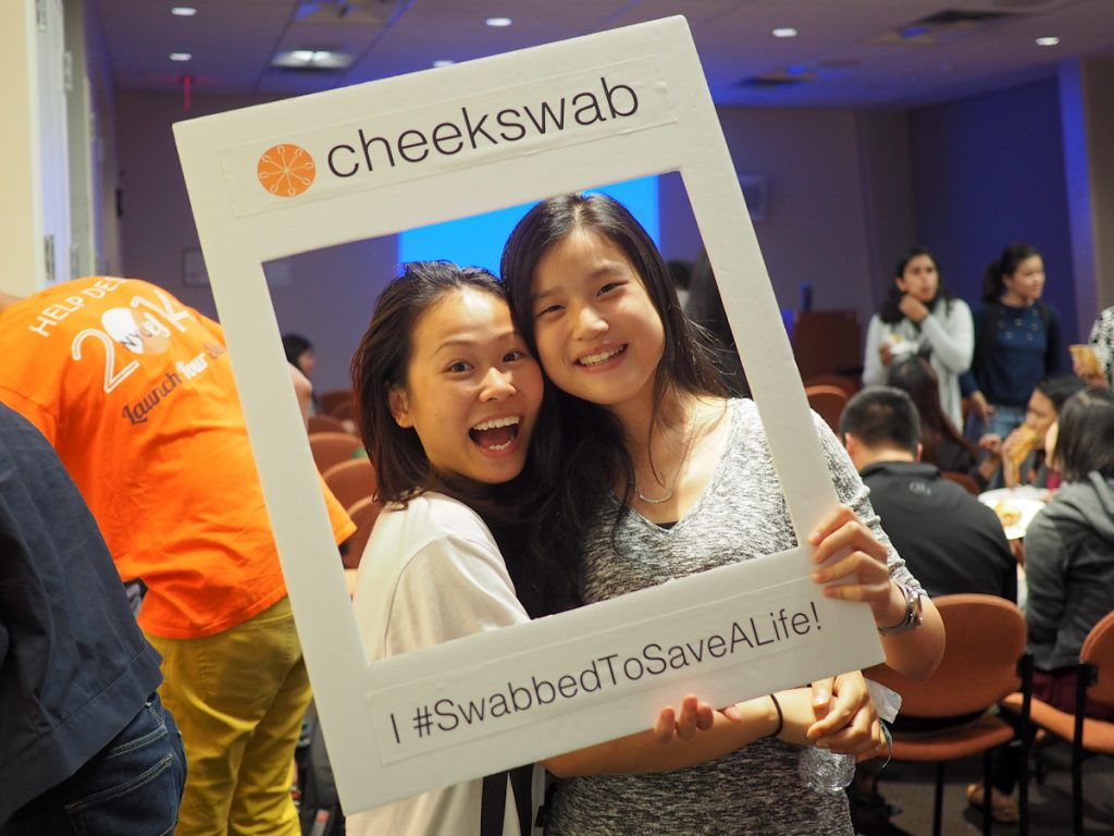 Two East Asian women smiling into Cheekswab frame