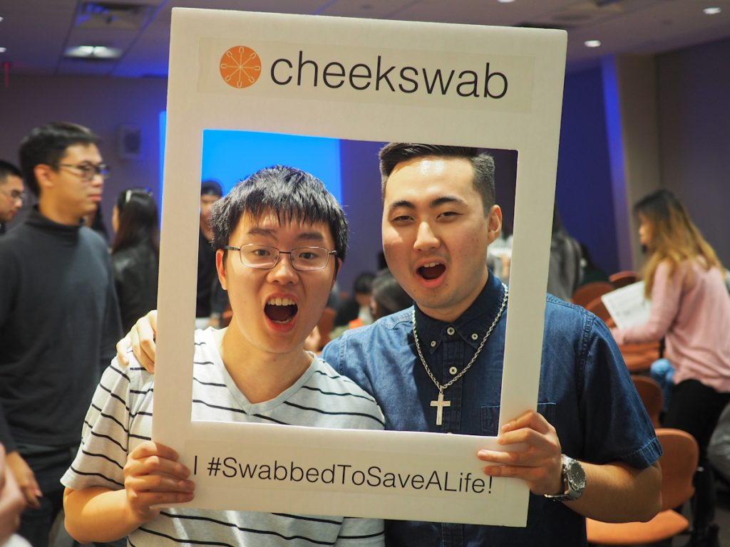 Two East Asian men smiling into Cheekswab frame